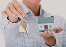 A man holding a toy house and holding out a set of keys